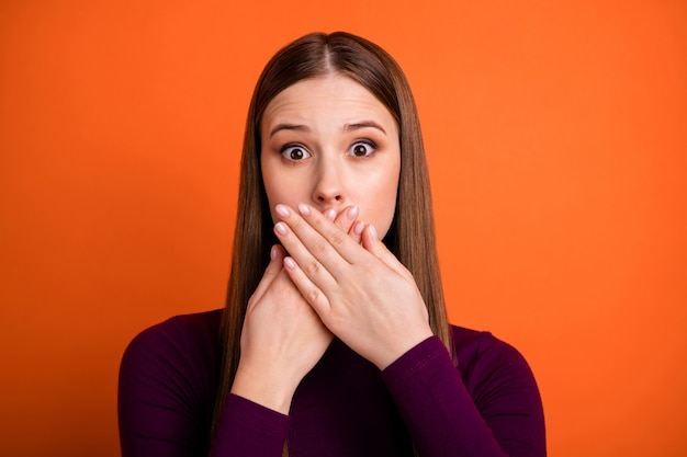 Close up portrait of frustrated upset girl close cover hand mouth make mistake share secret wear good look violet pullover isolated over bright shine color background