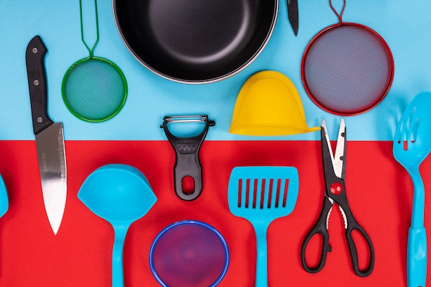 Close up portrait of frying pan with set of kitchen utensils on red-blue