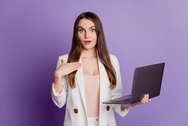 Close up portrait of funky carefree positive lady hold computer hand chest on violet wall
