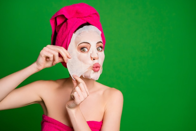 Close-up portrait of funky lady wearing turban removing ugly essence facial mask home procedure isolated on bright green color background
