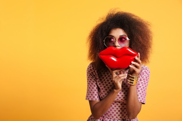 Close-up portrait of funny afro american wooman in sunglasses holding big red lips in front of her face, looking aside