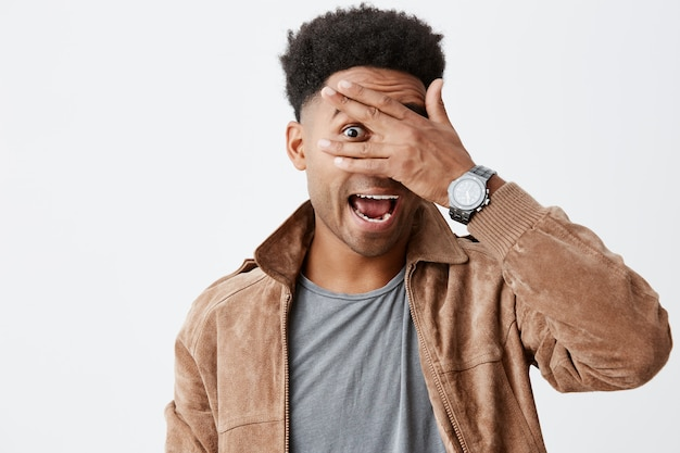 Close up portrait of funny beautiful black skinned man with afro hairdo in grey t-shirt under brown jacket looking through fingers in camera with happy and excited face expression.