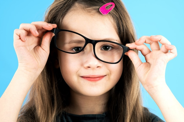 Close up portrait of a funny child school girl wearing looking glasses isolated on blue background.