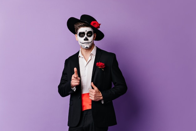 Close-up portrait of funny guy with skeleton mask, showing finger to camera.