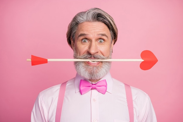 Close-up portrait of funny man holding in teeth arrow