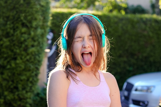Close-up portrait of funny preteen girl with wireless headphones on head