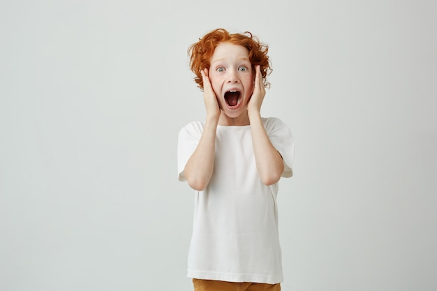 Close up portrait of ginger beautiful little boy with freckles holding head in hands and screaming when his friend scared him.