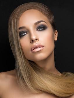 Close up portrait of girl on black background. evening makeup. smoky eyes. hi-end retouch