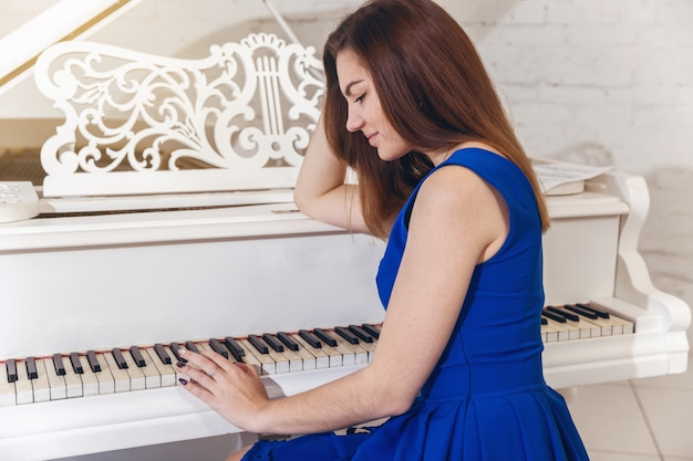Close-up portrait of a girl in a blue dress sitting at the piano and touches the piano keys