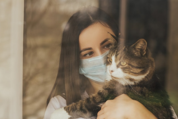 Close up portrait of girl is standing with a cat at home near window in a protective mask from the virus.