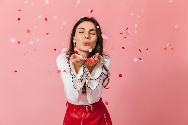 Ritratto del primo piano della ragazza in gonna di pelle che invia bacio dell'aria su sfondo rosa con coriandoli.
