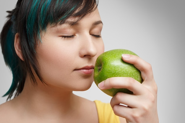 Close-up portrait. a girl smelling an apple.