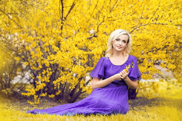 Close-up portrait of a girl with professional makeup. beautiful woman in a purple dress with blooming forsythia.