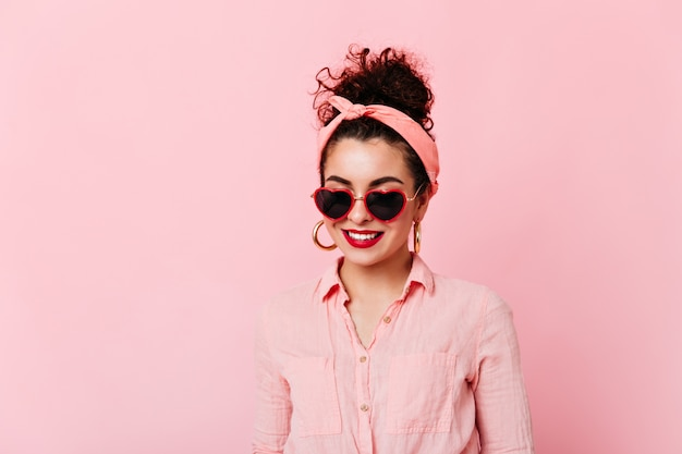 Close-up portrait of girl with red lips and bun in sunglasses. woman in pink headband and cotton shirt is smiling on isolated space.