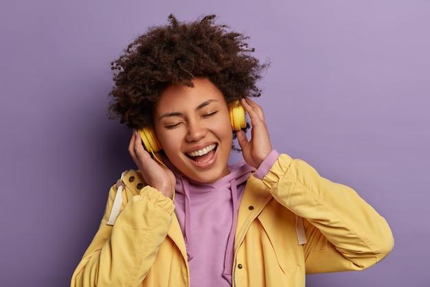 Close up ritratto di felice e divertente donna dai capelli ricci ascolta la musica preferita con le cuffie