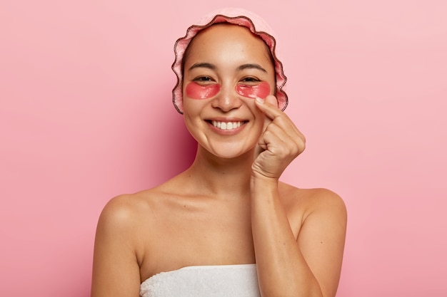 Close up portrait of glad korean woman makes like sign, crosses thumb and index finger, sends love, wears pink bathcap, has cosmetology treatments under eyes, applies collagen patches for moisturizing
