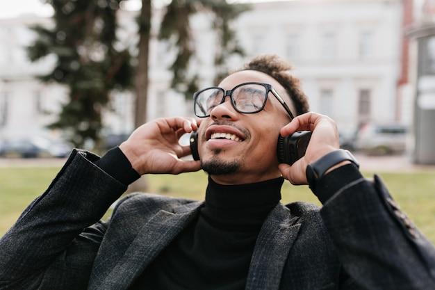 Close-up portrait of good-looking black boy laughing. photo of inspired brunette man wears elegant gray jacket and big headphones.
