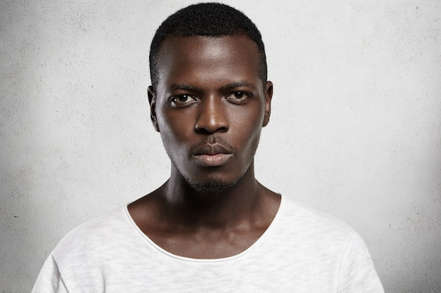 Close up portrait of good-looking serious african man with healthy clean skin wearing white casual t-shirt posing isolated against gray  wall with copy space for your promotional content