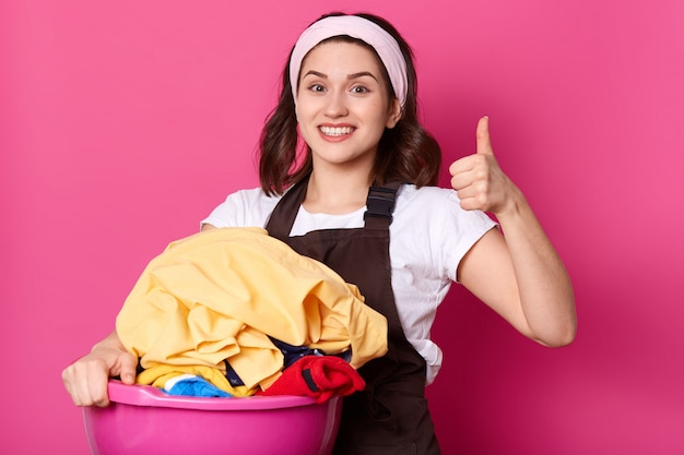 Close up portrait of good looking slender housewife holding pink basin with clean clothes, having positive facial expression, showing super sign with her fist and thumb, looks emotional and happy.