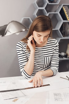 Close up portrait of good-looking young female architect freelancer with dark long hair in striped shirt sitting at white table in coworking space, looking through blueprints she already made, thinkin