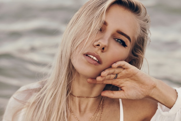 Close up portrait of gorgeous blond woman with perfect skin and blue eyes posing on the beach