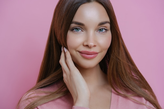 Close up portrait of gorgeous european woman with healthy perfect skin, touches her well cared hair