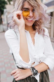 Close-up ritratto di splendida bionda giovane donna indossa elegante orologio da polso e bracciale d'argento