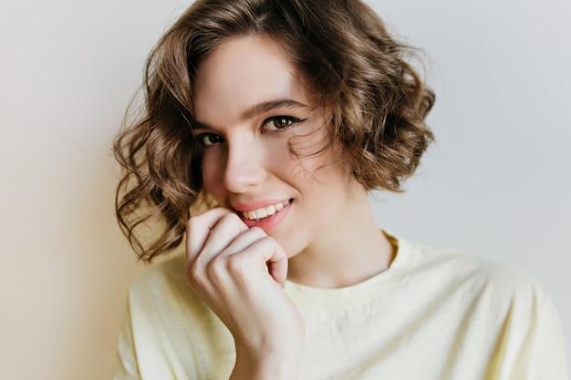 Ritratto del primo piano del modello femminile splendido con i begli occhi. incredibile ragazza dai capelli scuri in camicia bianca in posa con il sorriso sulla parete chiara.