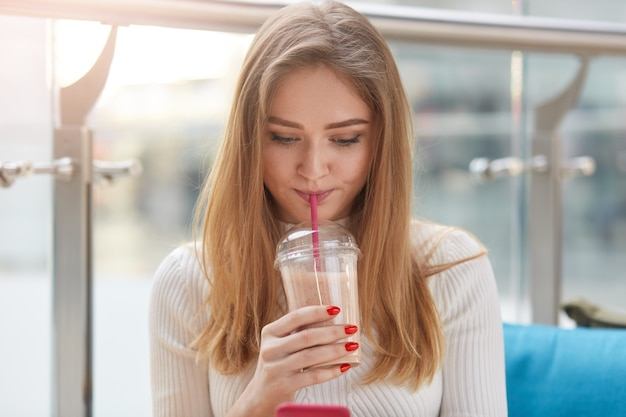 クローズアップホワイトカジュアルシャツのゴージャスな肖像画の女の子は、夏のカフェに座ってカクテルを飲んで、ロンゲブロンドの髪を持っています。