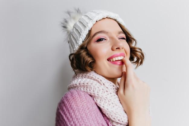 Ritratto del primo piano della splendida ragazza in posa giocosamente in cappello invernale. foto dell'interno della donna castana sognante in sciarpa che sta sulla parete chiara.