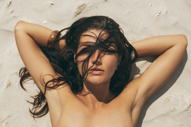 Close-up portrait of gorgeous mixed race caucasian asian woman laying naked on the beach on vacations outdoors. top view