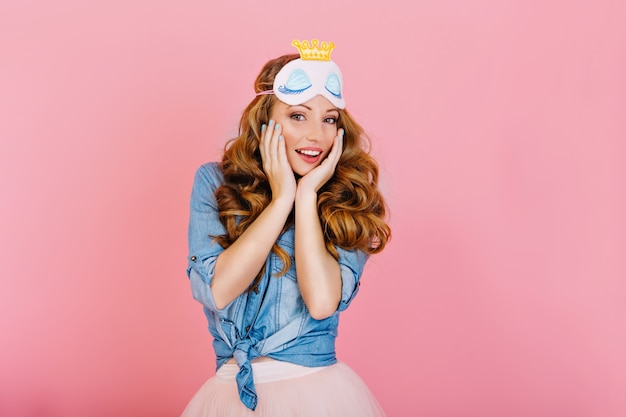 Close-up portrait of graceful curly girl in sleep mask and denim retro shirt, posing with hands touching face. beautiful long-haired girl in stylish outfit standing with surprised face expression