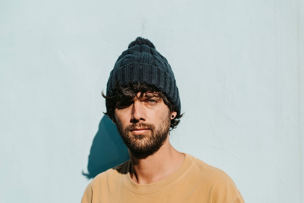 A close up portrait of a green eyes young male with beanie, beard and t-shirt.