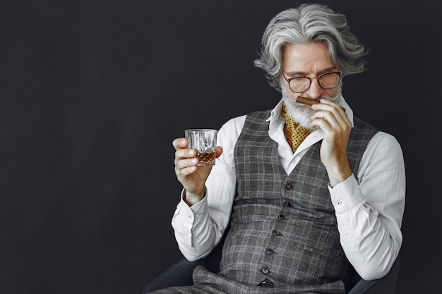 Close up portrait of grinning old-fashioned man.  grandfather with a cigar and whiskey.
