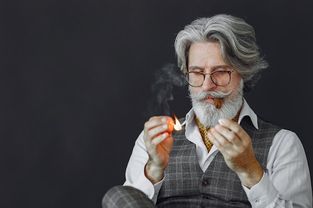 Close up portrait of grinning old-fashioned man.  grandfather with a cigar.