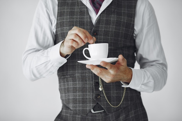 Close up portrait of grinning old-fashioned man.  grandfather with a mug of tea.