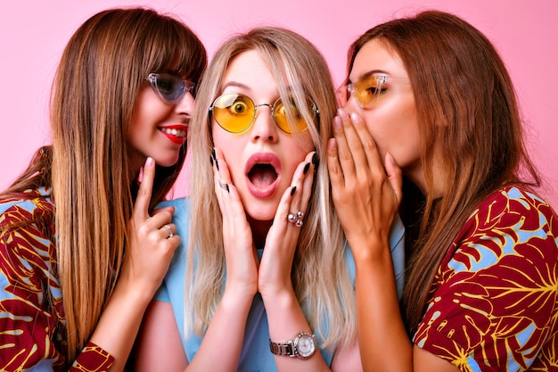 Close up  portrait of group funny stylish woman whispering secrets to each other, surprised exited emotions, trendy color matching clothes and glasses. happy friends having fun