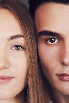 Close up portrait of half faces man and woman looking at camera