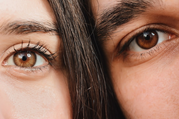 Close up portrait of half faces man and woman looking at camera.