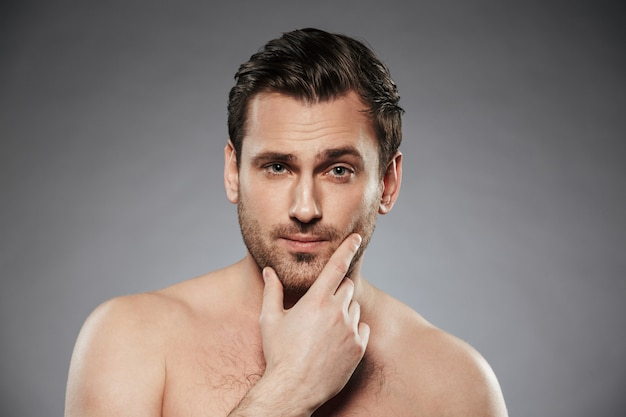 Close up portrait of half naked bearded man with hand on his chin, isolated over gray wall