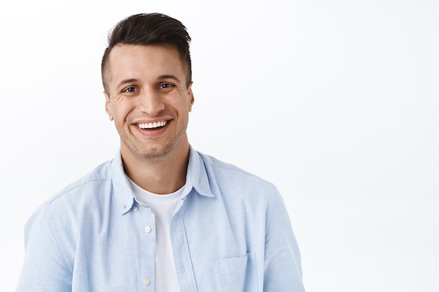 Close-up portrait of handsome adult man with beaming smile,  satisfied, feel upbeat and enthusiastic, standing white wall cheerful, enjoying the day, feel excitement