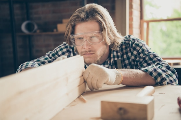 Close-up portrait of handsome bearded craftsman posing in his woodshop