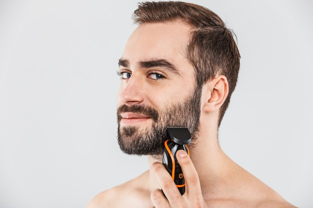 Close up portrait of a handsome bearded man shaving with an electric razor isolated over white