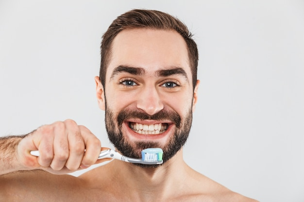 Close up portrait of a handsome bearded man standing isolated over white, brushing his teeth