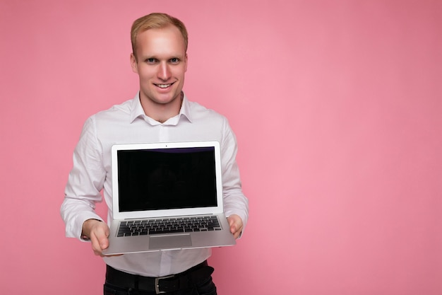 Close-up portrait of handsome blonde man holding computer laptop looking at camera isolated over pink background.