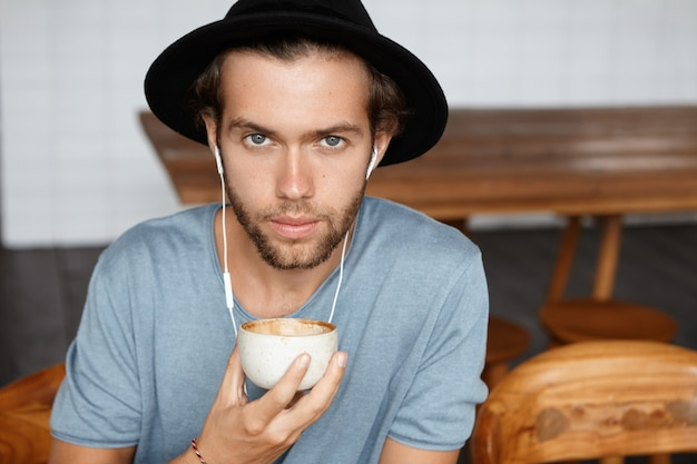 Close up portrait of handsome blue-eyed young man with stylish beard wearing black hat and casual t-shirt holding mug of cappuccino and looking while enjoying good music on earphones
