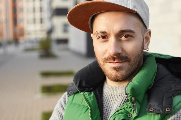 Close up portrait of handsome charismatic guy with brown eyes, bristle and pierced earrings waiting for girlfriend outdoors with smile. people, lifestyle and urban fashion concept