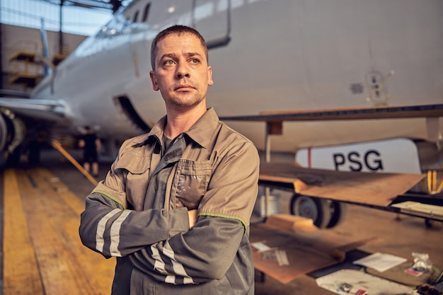 Close up portrait of handsome confident aviation engineer in uniform keeping arms crossed while standing on front of big commercial aircraft