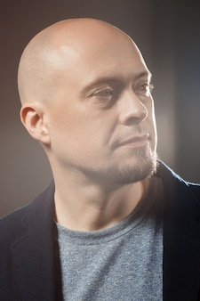 Close up portrait of handsome confident middle-aged businessman looking away over black flare background.