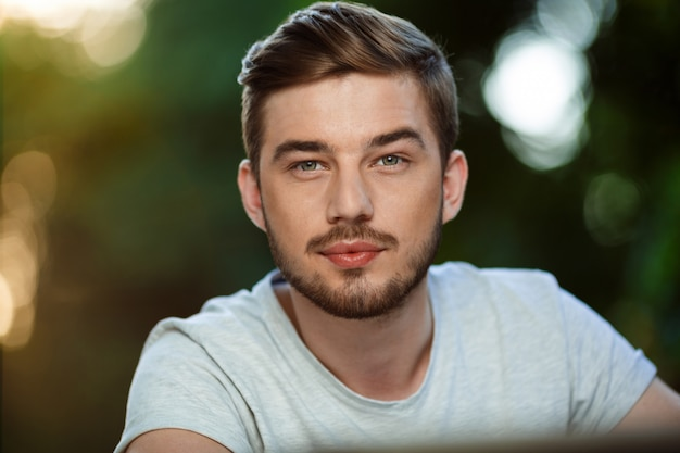 Close up portrait of handsome confident young man in white t-shirt on blurry outdoor nature